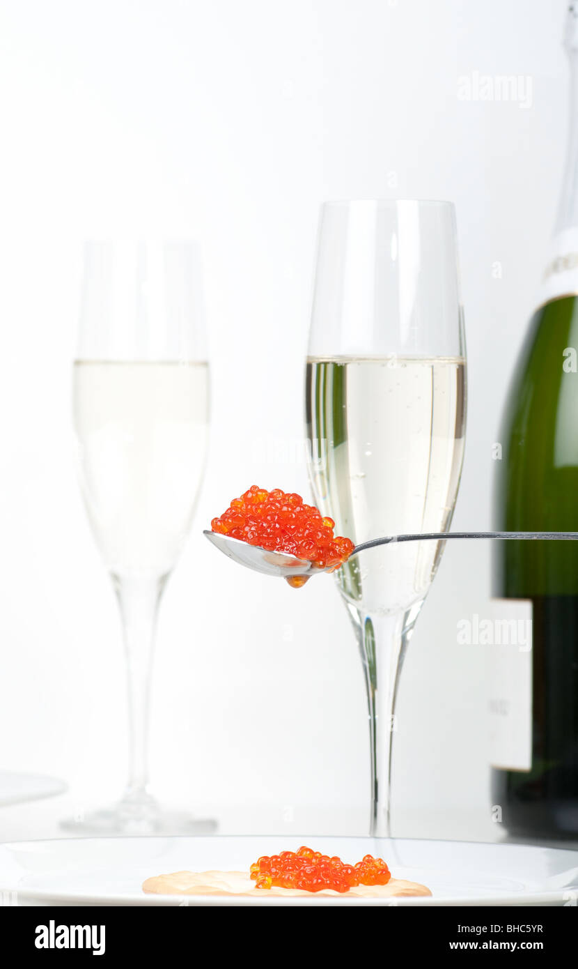 A  spoon with salmon caviar in front of full champagne glasses and a bottle of champagne. Focus on caviar. - Stock Image