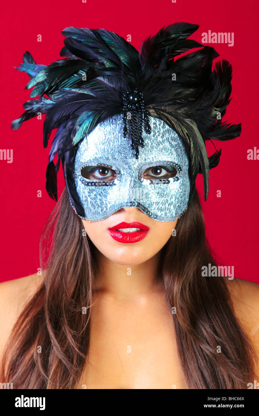 Beautiful brunette woman wearing a masqurade mask against a bright red background. - Stock Image