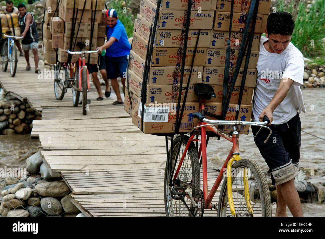 Colombian smugglers push bicycles loaded with the Venezuelan contraband on an illegal bridge on the Colombian-Venezuelan - Stock Image