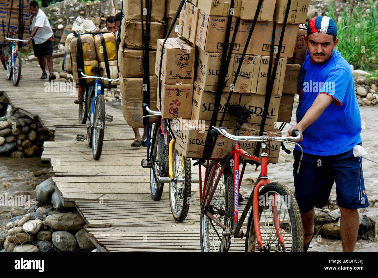 Colombian smugglers pushing bicycles fully loaded with the Venezuelan contraband on an illegal bridge across the - Stock Image