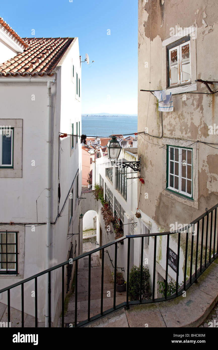 One of the narrow streets of Alfama with the typical cobblestone staircases (Beco da Corvinha). Alfama,  Lisbon, - Stock Image