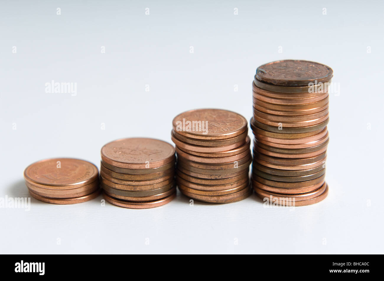 4 Stacks of coins shot on a white background. Each stack increases in size. - Stock Image