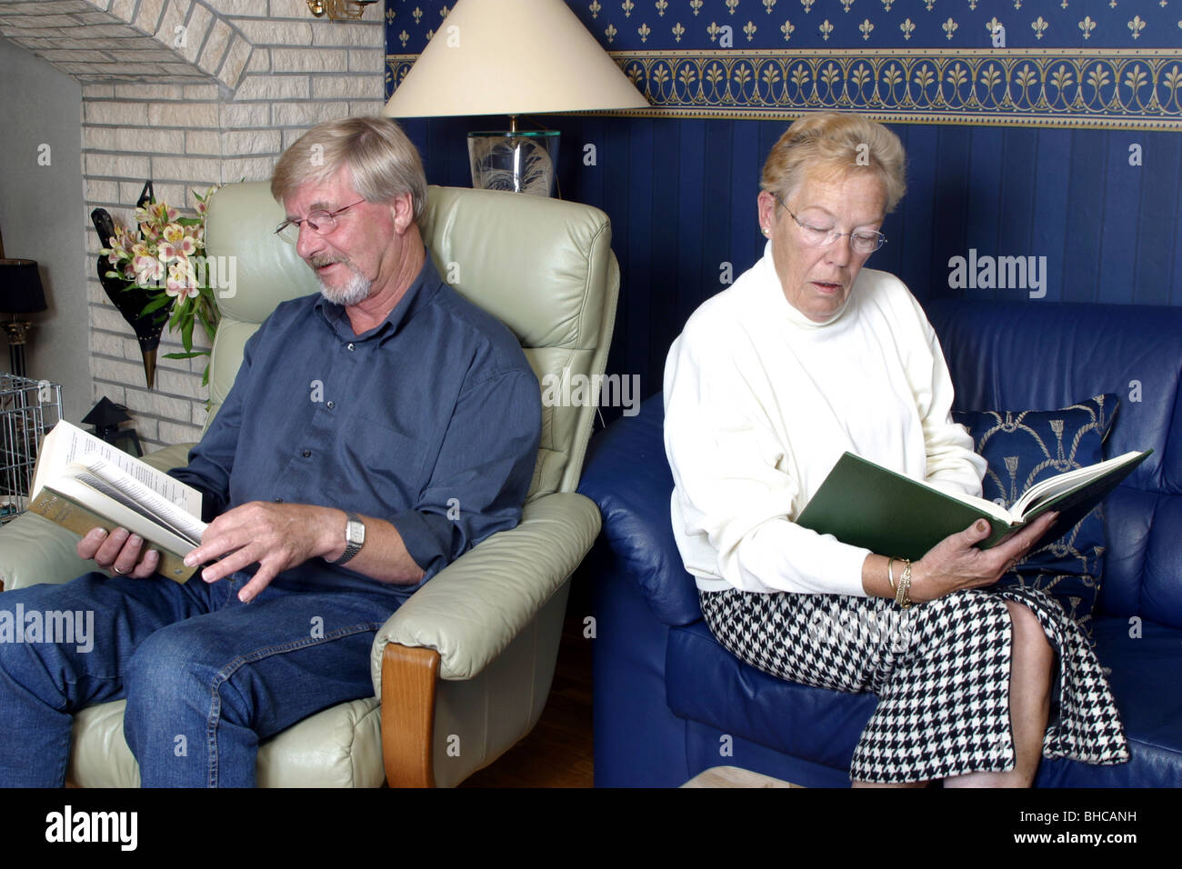 Middle aged couple back to back nothing to say reading a book - Stock Image