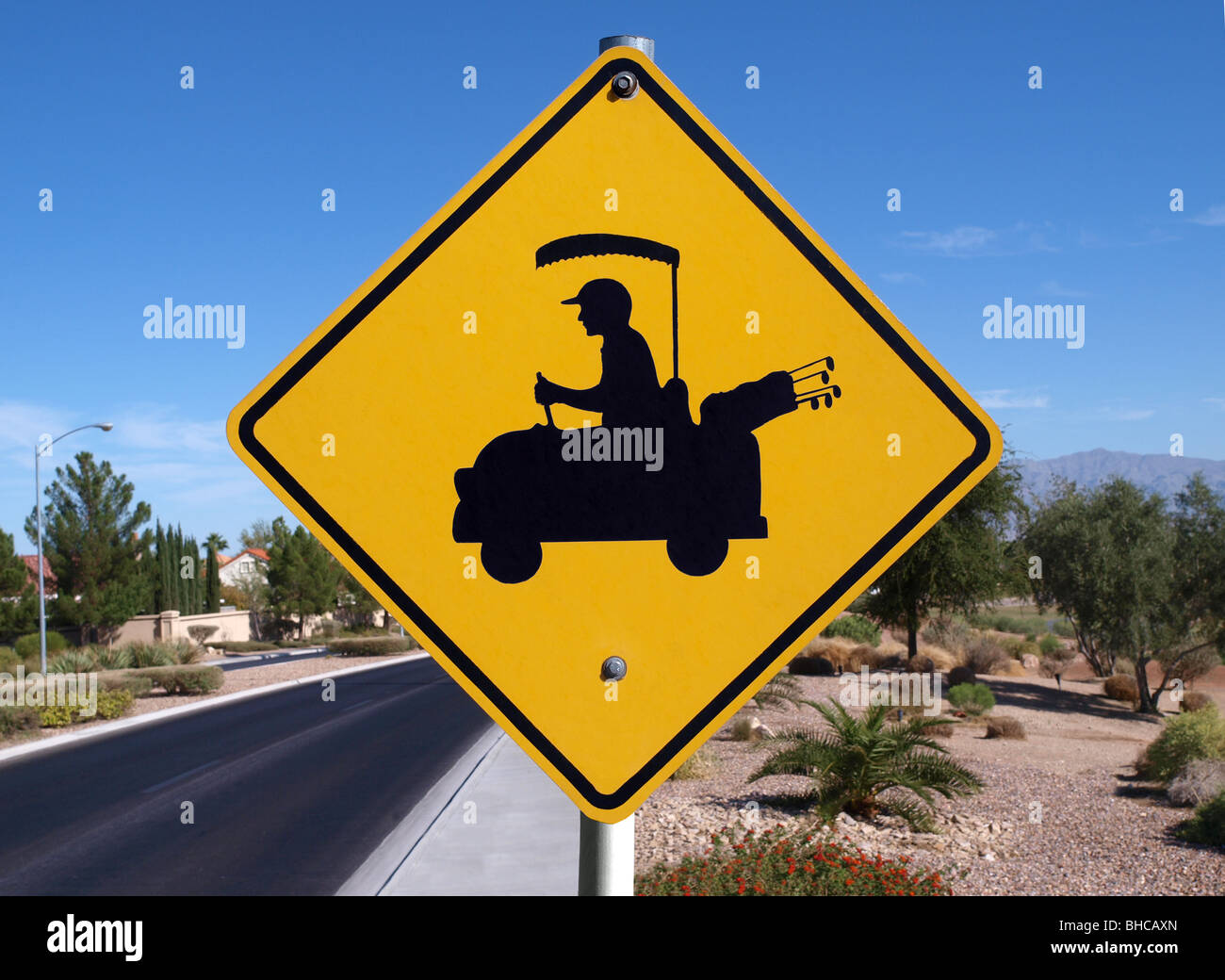 Golf cart crossing sign in a affluent desert community. - Stock Image