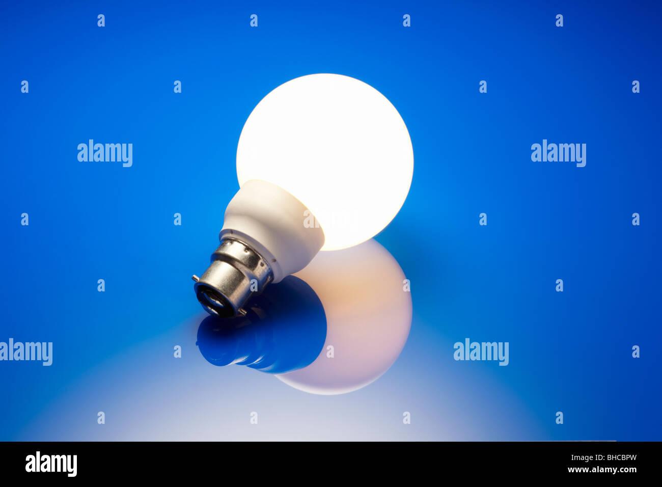 Energy Saving Bulb Illuminated - Stock Image