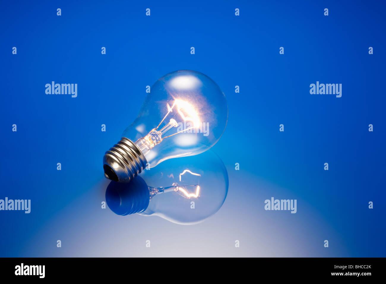 Clear Standard Light Bulb Illuminated - Stock Image
