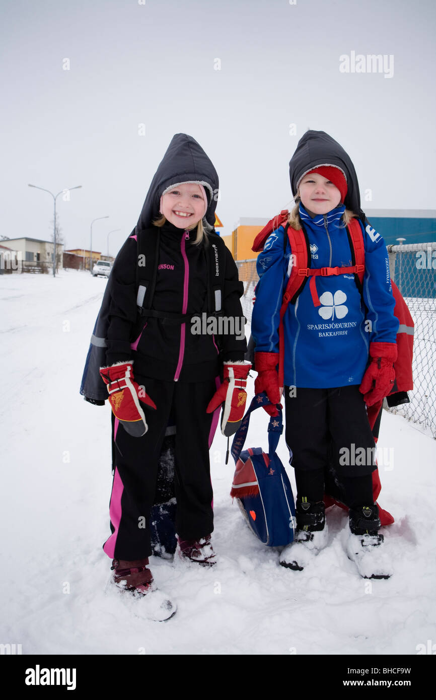 Asta (8) and Borghildur (7) on their way home from school. Vopnafjordur, East Iceland. - Stock Image