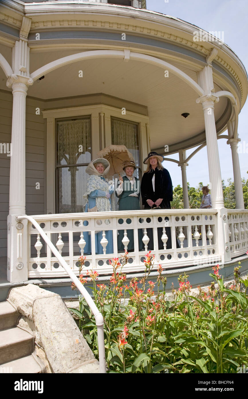 Women in Victorian dresses standing on porch of Faulkner Farm and Victorian home in Santa Paula, CA - Stock Image