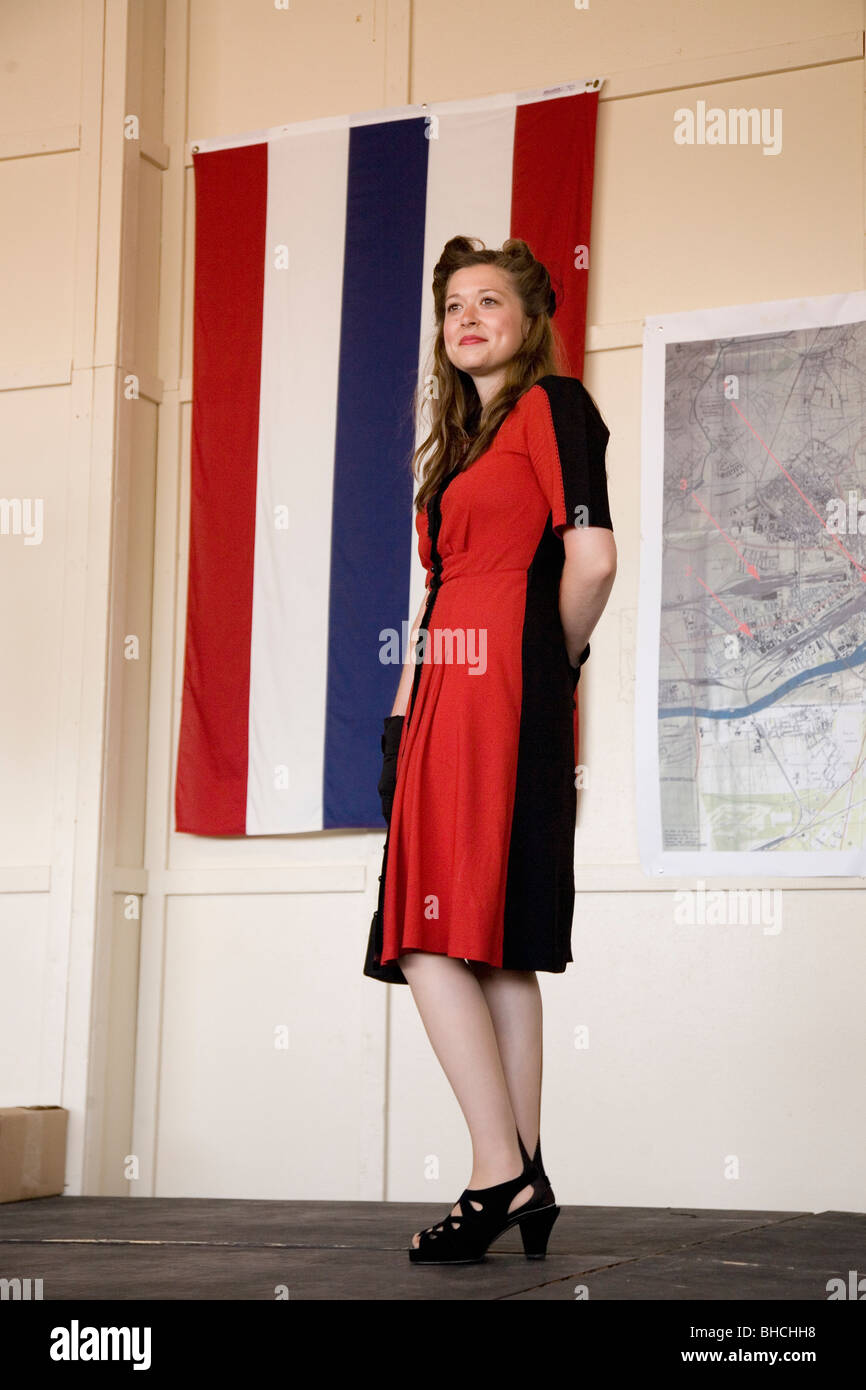 3decb9cf1b0 Attractive woman in 1940s clothing posing in front of flag during a  reenactment of a World
