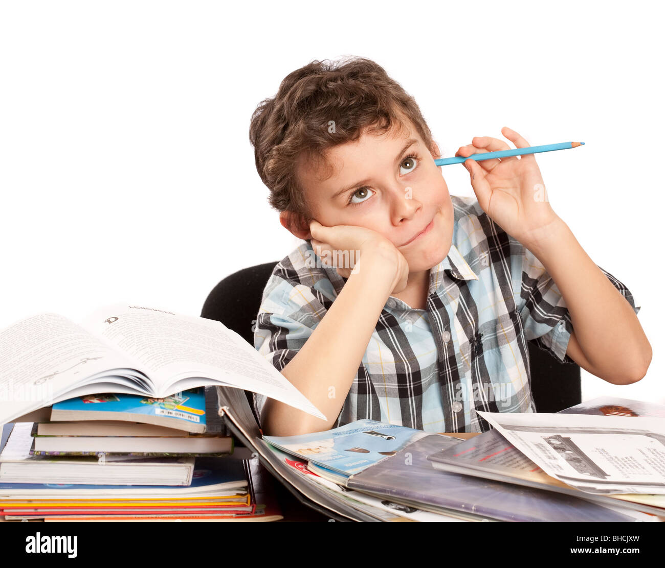 Portrait of a cute kid dreaming with his eyes open instead of doing his homework - Stock Image