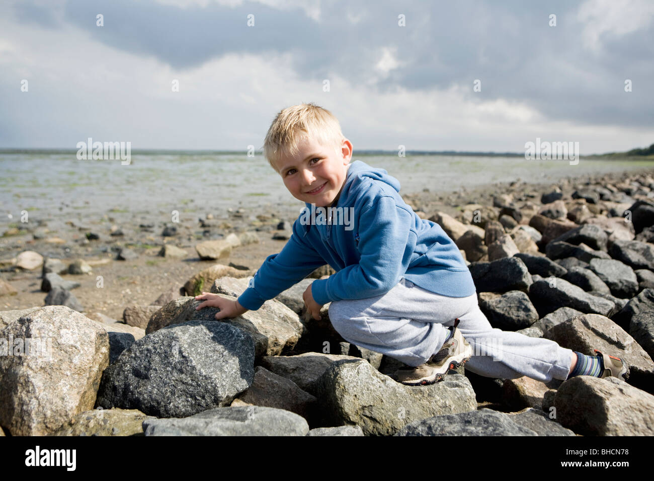 Boy walking over stones Stock Photo