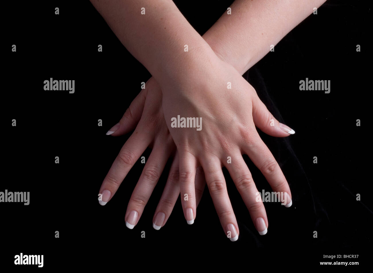 crossed hands with splayed fingers - Stock Image