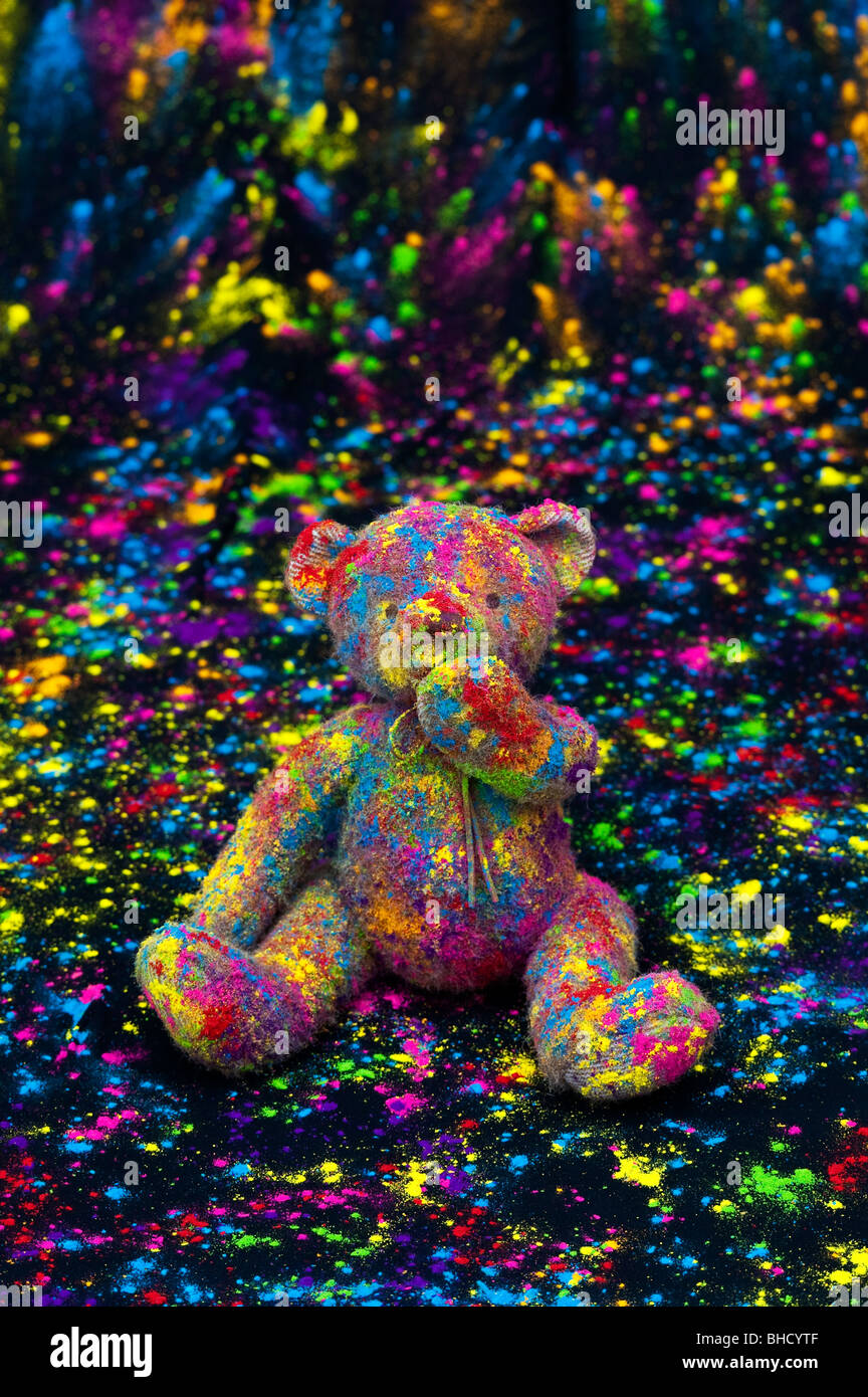 Teddy bear sat on a black cloth covered in coloured powder. Still life - Stock Image