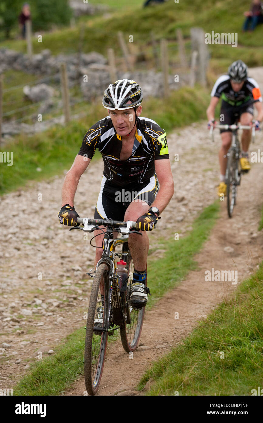 Cyclists ride a dirt trail during the Three Peaks Cyclo-Cross in Yorkshire, United Kingdom - Stock Image