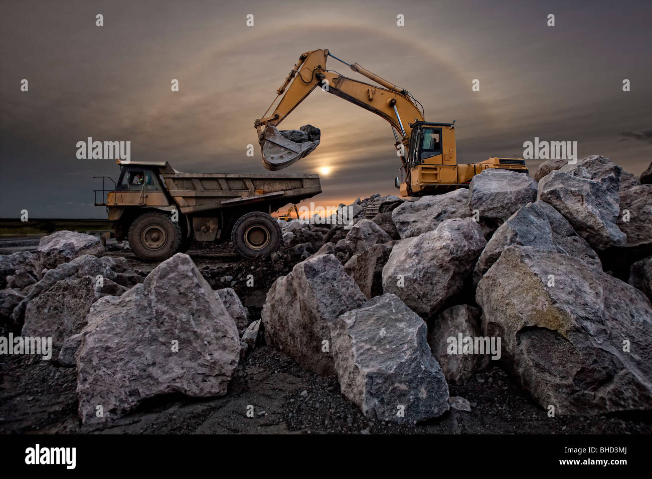 Digger and dump truck moving large boulders, Iceland Stock Photo