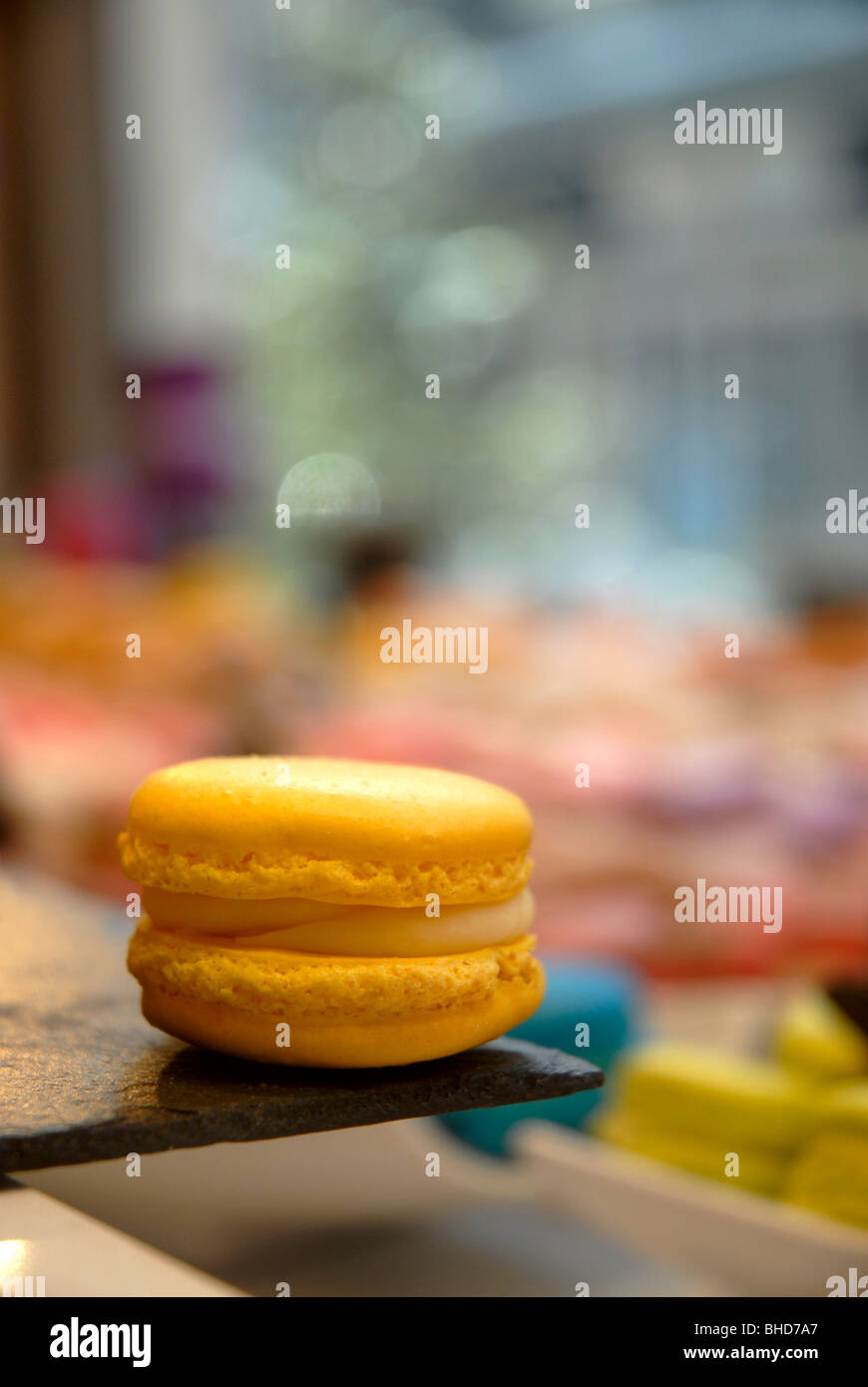 Multi colored Macaroons on display in shop window - Stock Image