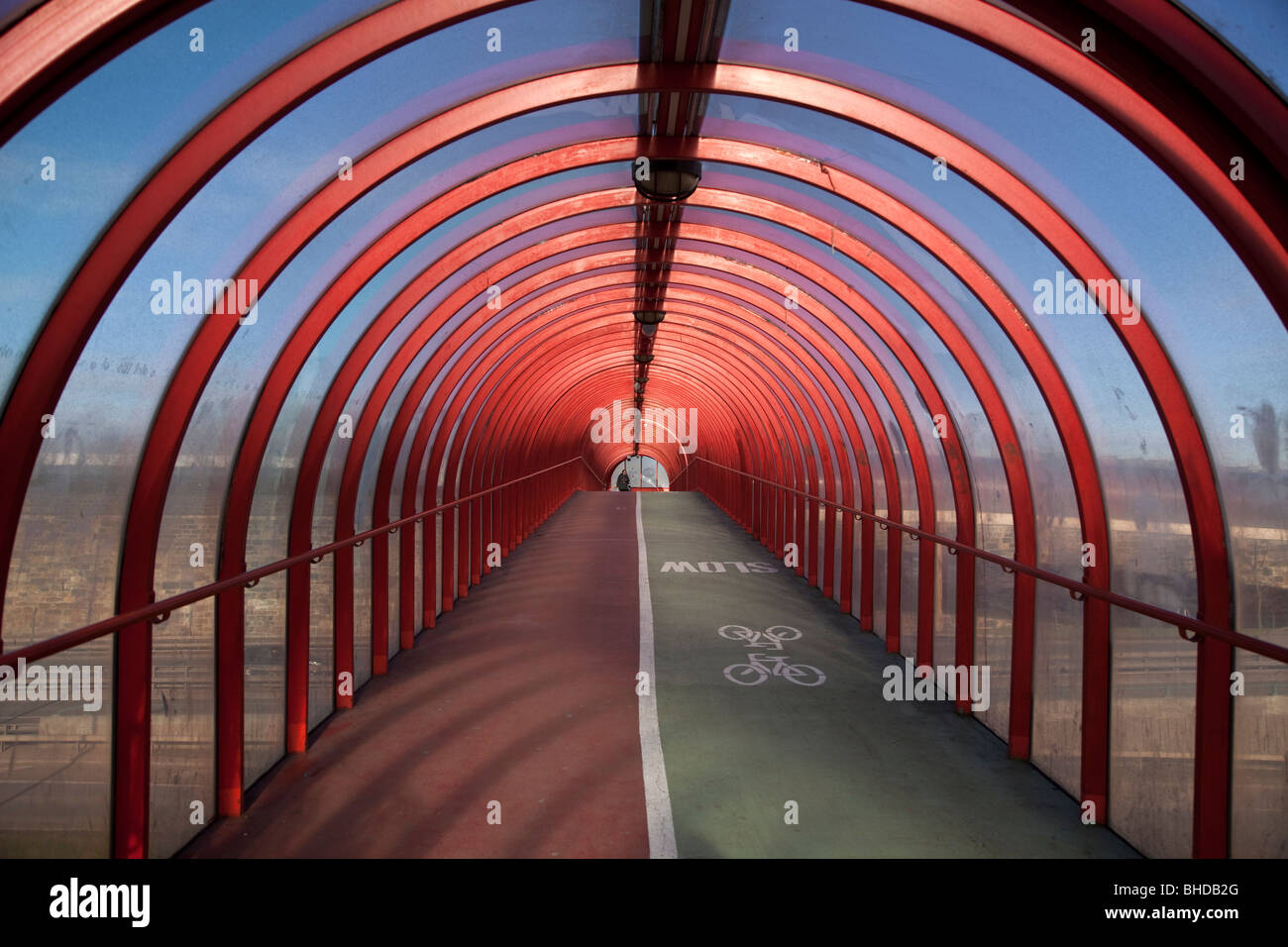 A view along an enclosed footbridge in Glasgow, Scotland. - Stock Image