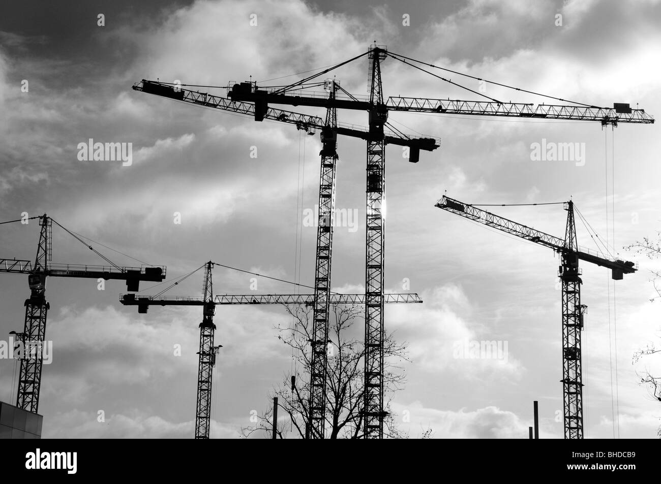 Several construction cranes on a building site signifying economic growth and rising industrial activity - Stock Image