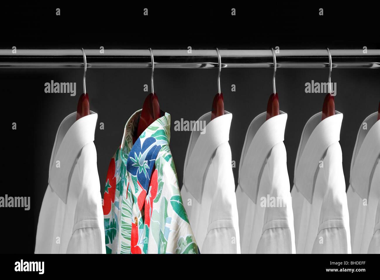 Tropical shirt between white shirts hanging inside a closet - Stock Image