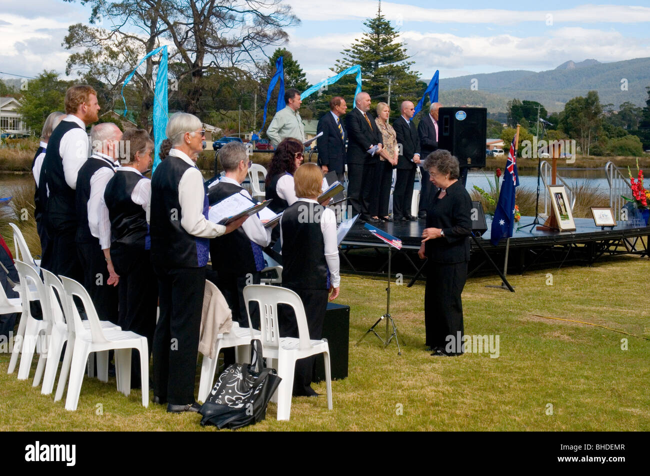 A choir leads singing of the national anthem at an Australian citizenship ceremony staged outside Hobart, Tasmania - Stock Image
