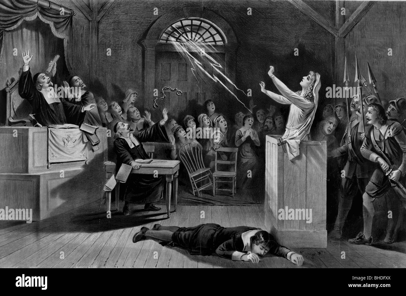 A dramatic scene from a witch trial with a woman conjuring power and a man passed out on the floor. Salem Witch - Stock Image
