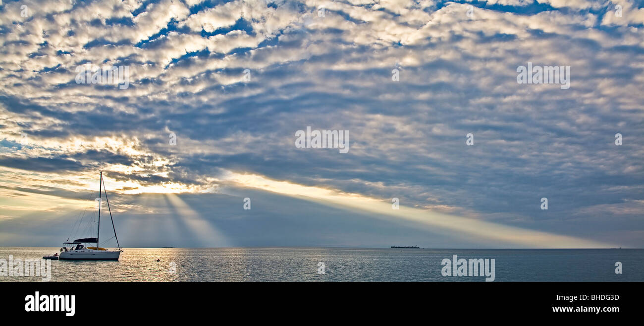 sun rays and sail boat in Belize - Stock Image