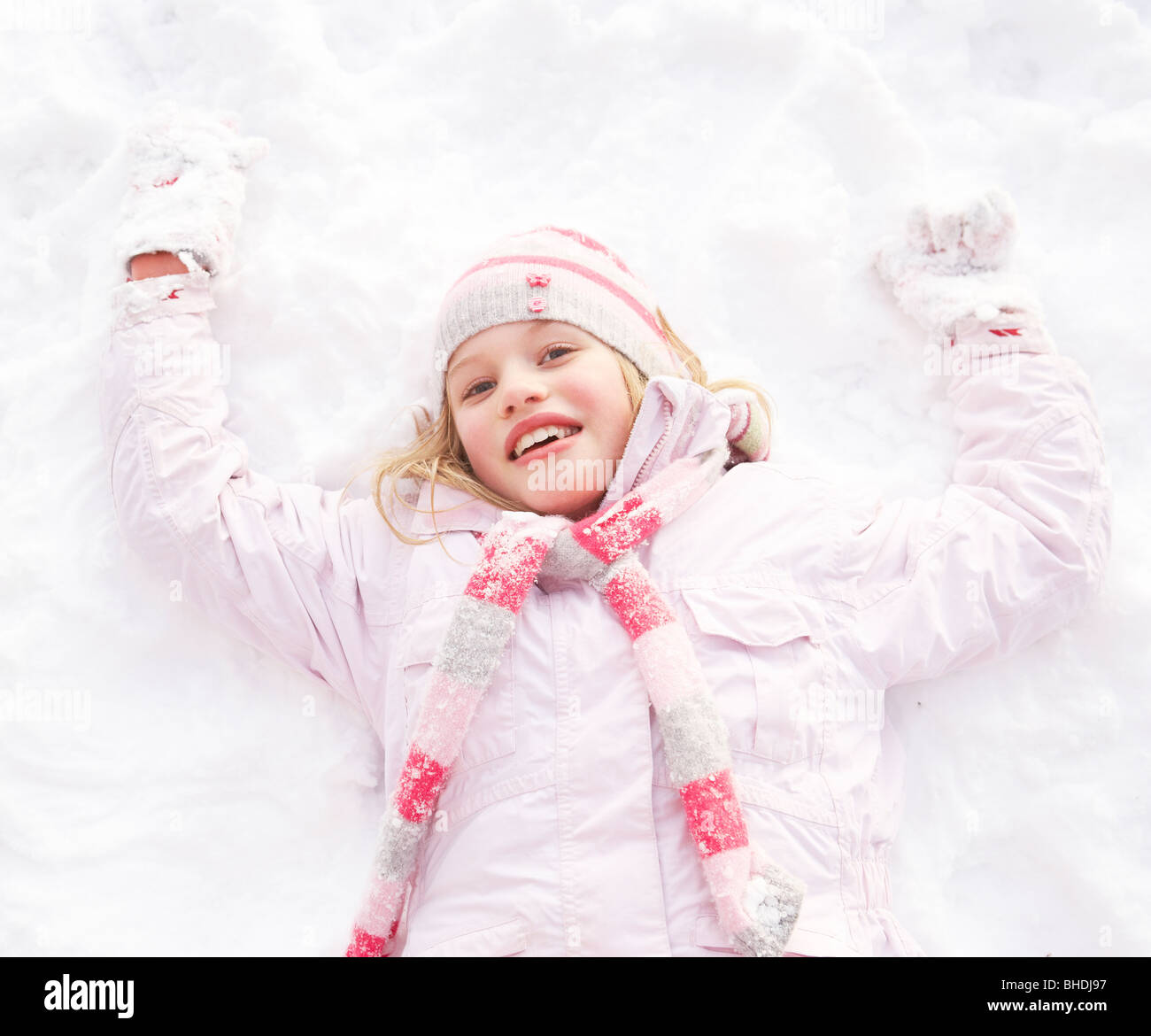 Girl Laying On Ground Making Snow Angel - Stock Image
