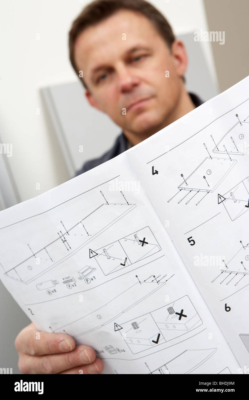 Man Reading Assembly Instructions For Flat Pack Furniture - Stock Image