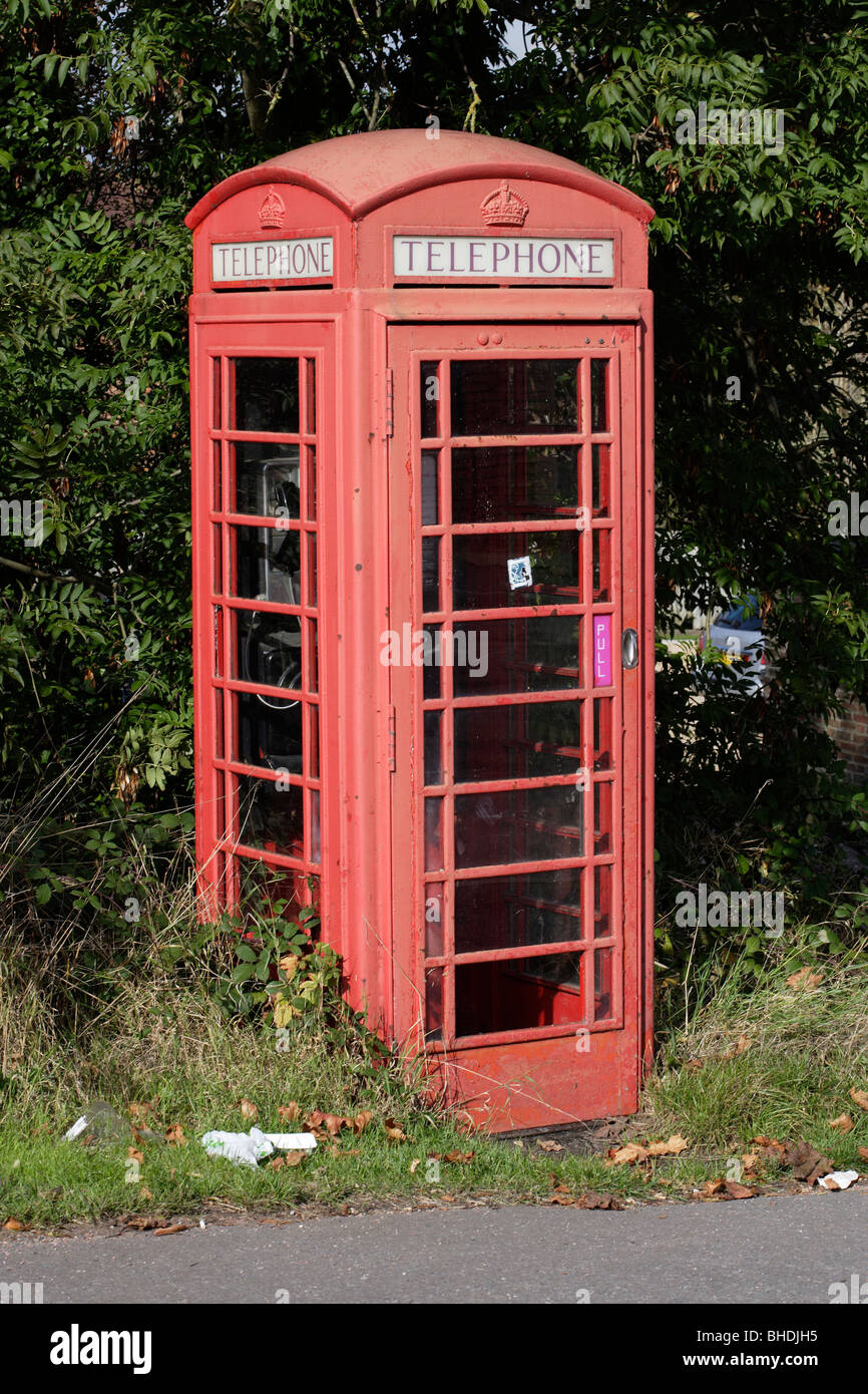 Old faded decayed red telephone box in England UK - Stock Image