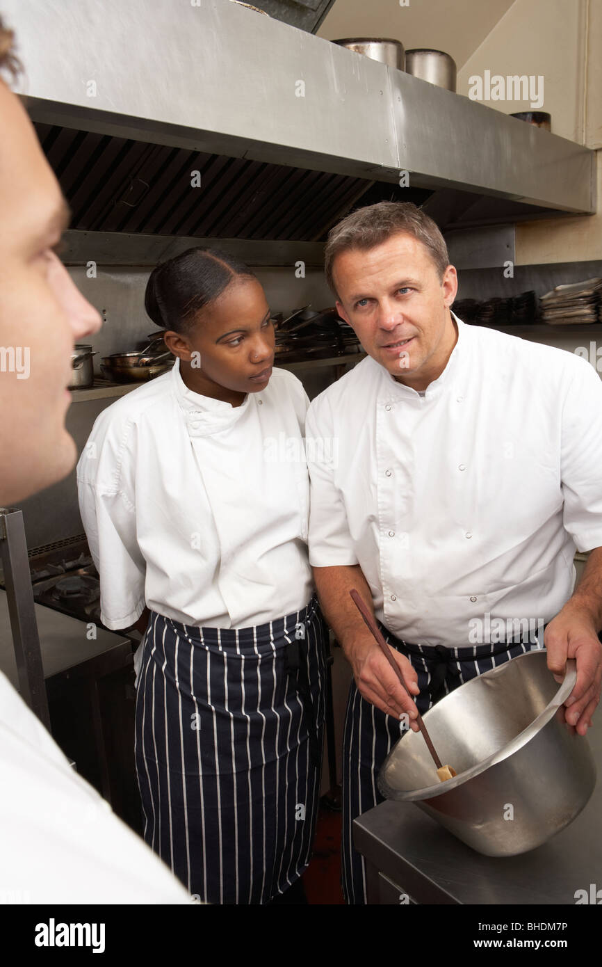 Chef Instructing Trainees In Restaurant Kitchen - Stock Image