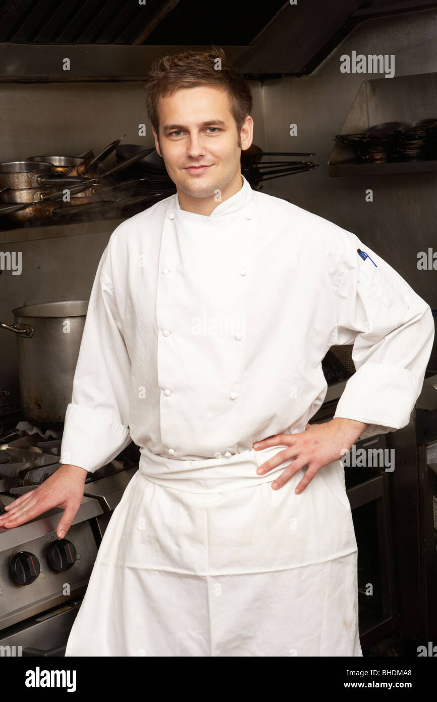 Male Chef Standing Next To Cooker In Restaurant Kitchen - Stock Image