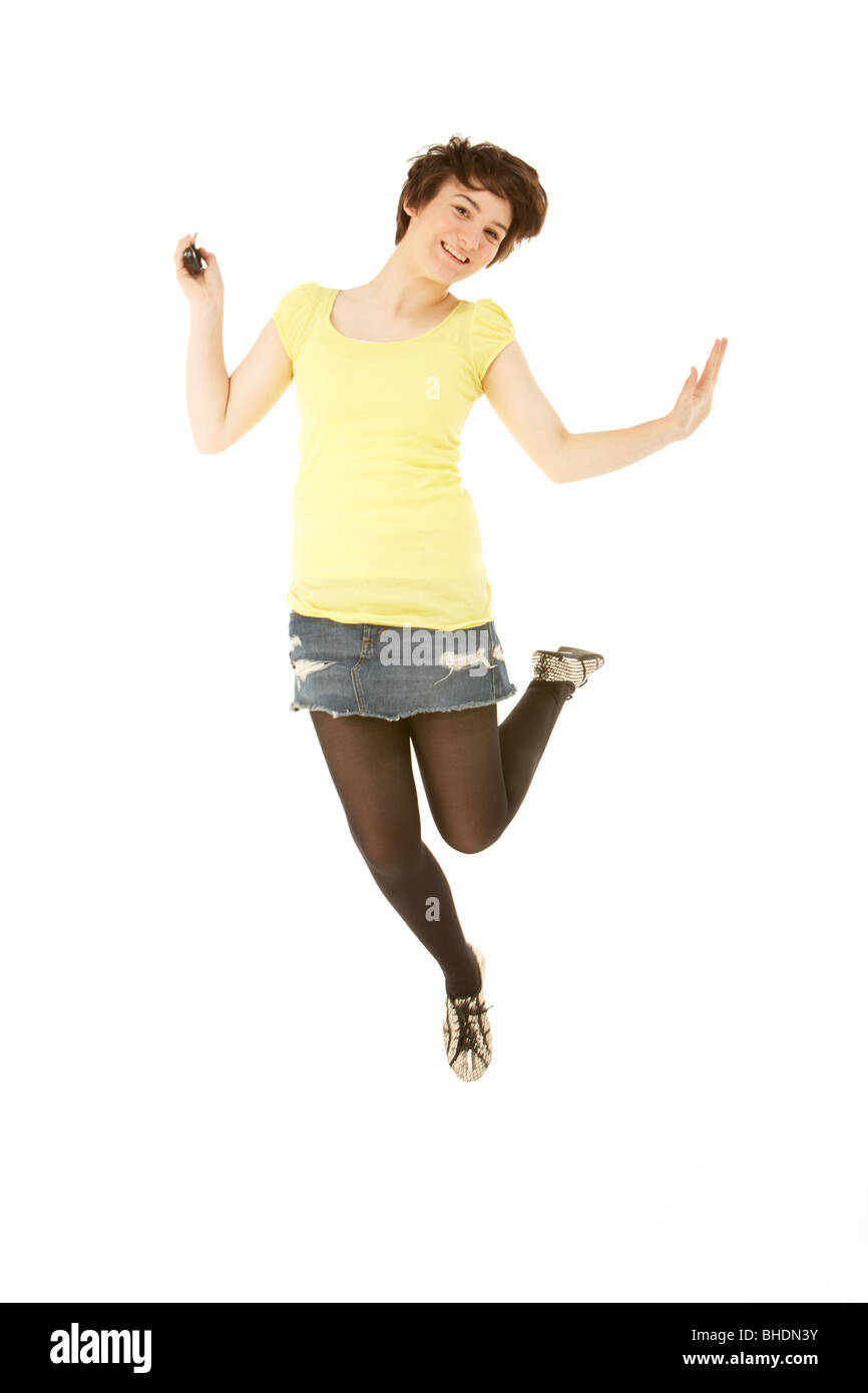 Studio Portrait Of Teenage Girl Jumping In Air - Stock Image