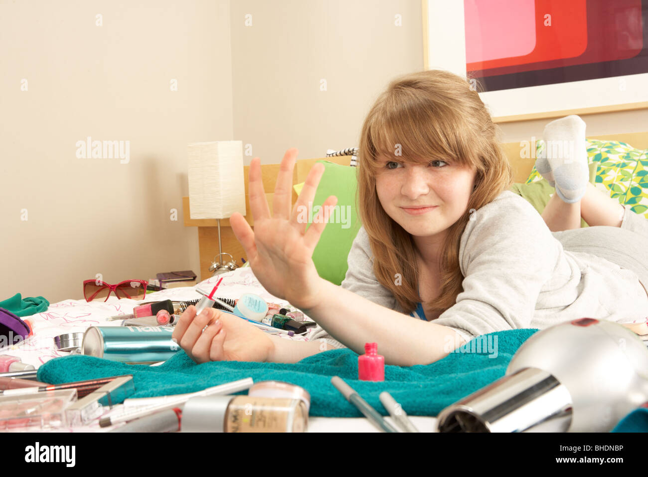 Teenage Girl In Untidy Bedroom Painting Nails - Stock Image