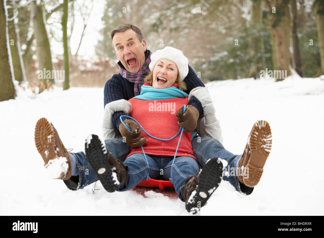Senior Couple Sledging Through Snowy Woodland - Stock Image