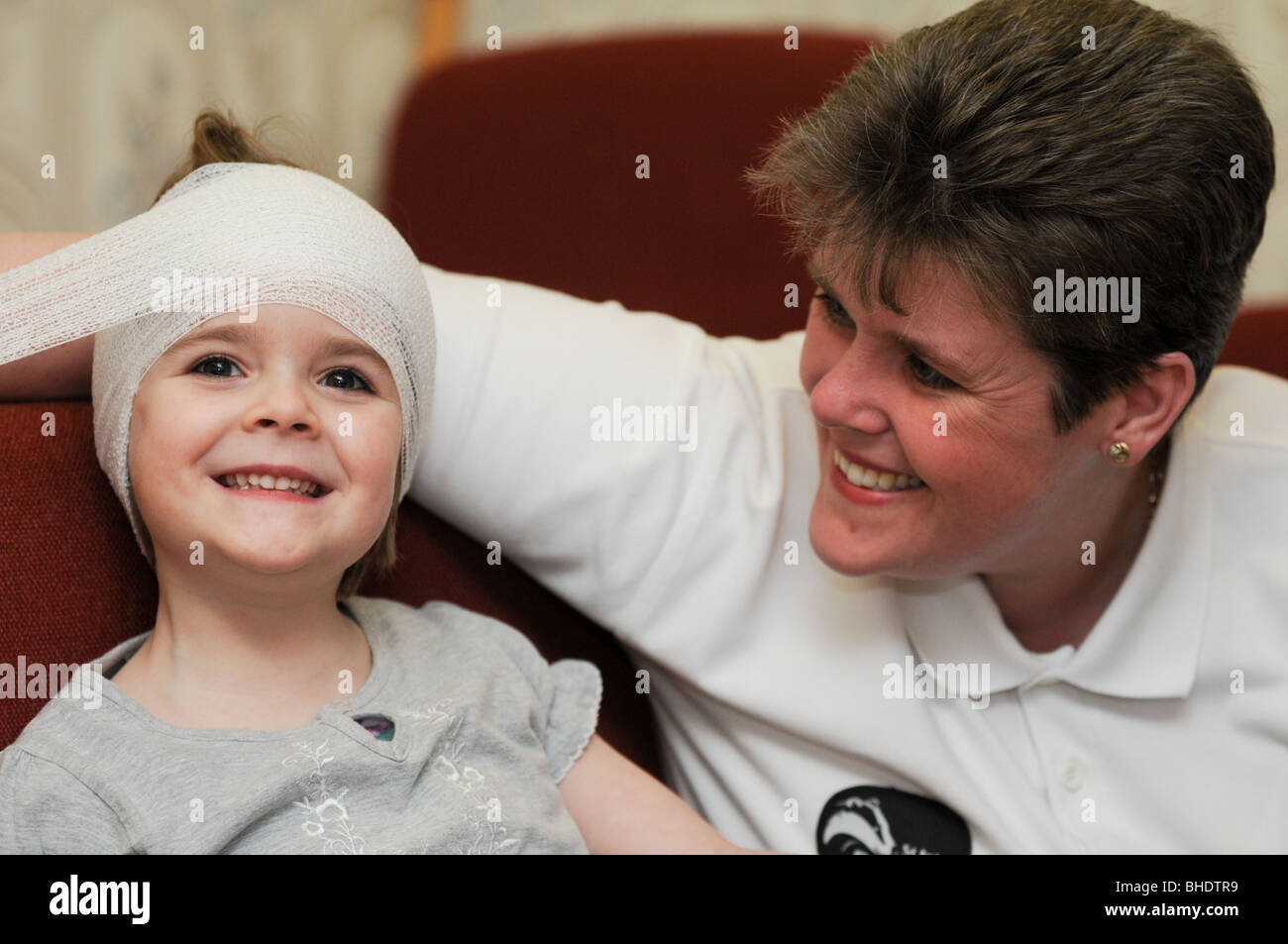 First aid practice being carried out on a little girl who is smiling at her first aider as she wraps a bandage around - Stock Image