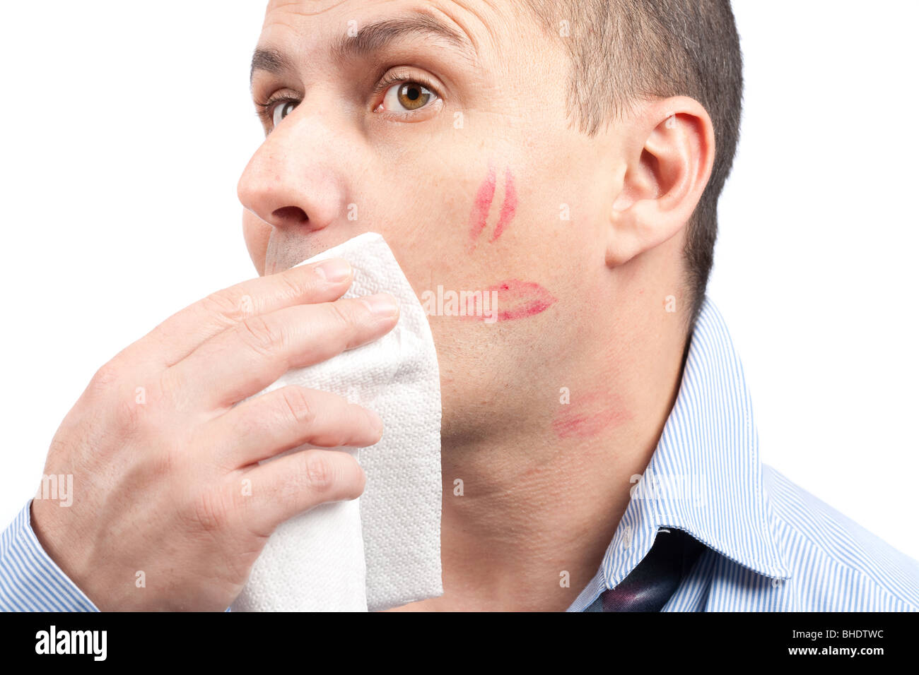Portrait of a young man erasing lips traces from his face - Stock Image