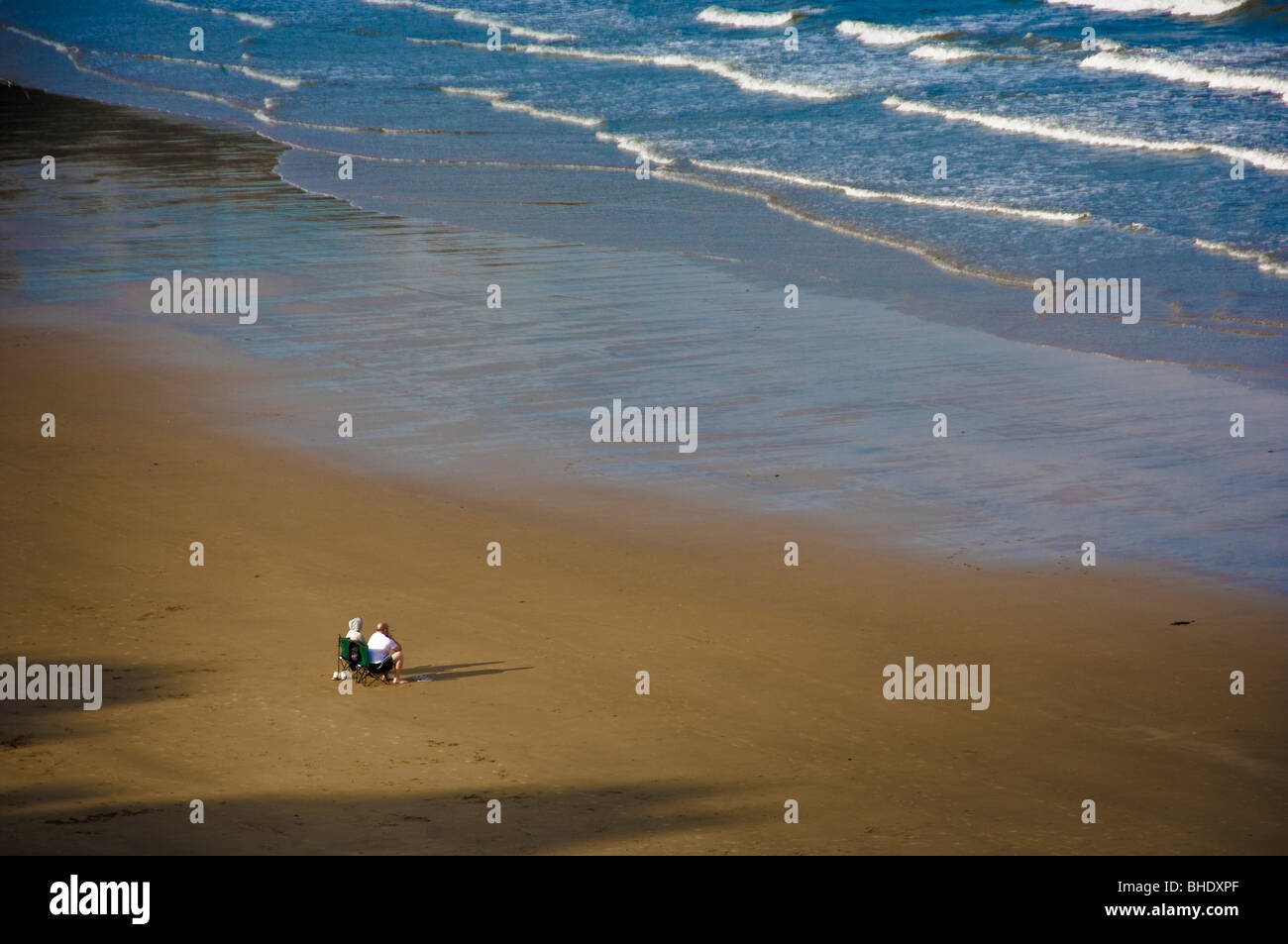 Couple on deserted beach looking out to sea - Stock Image