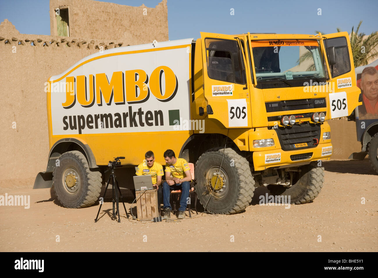 Man working on a laptop by a Desert racing truck at the Yasmina ...