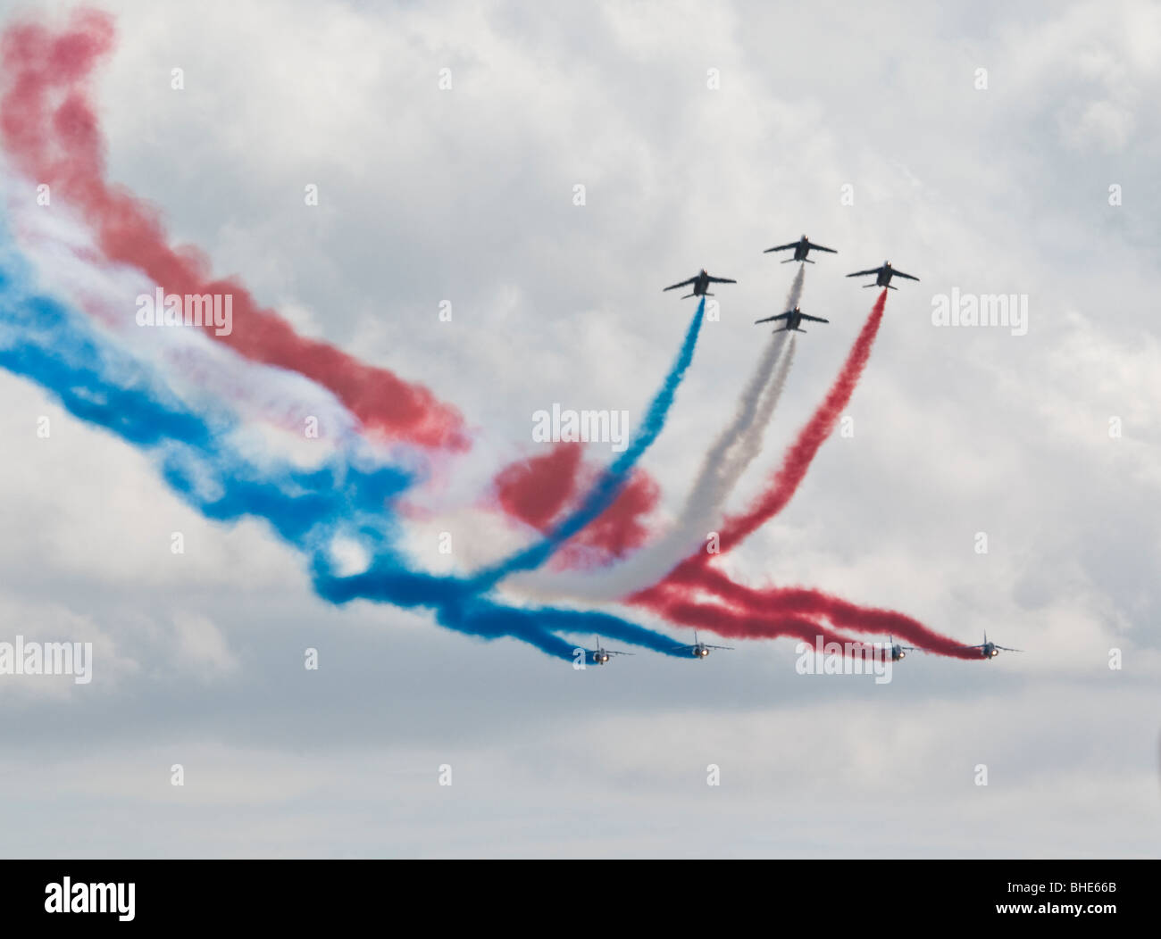 French Aerobatic display team flying in close formation trailing coloured smoke - Stock Image