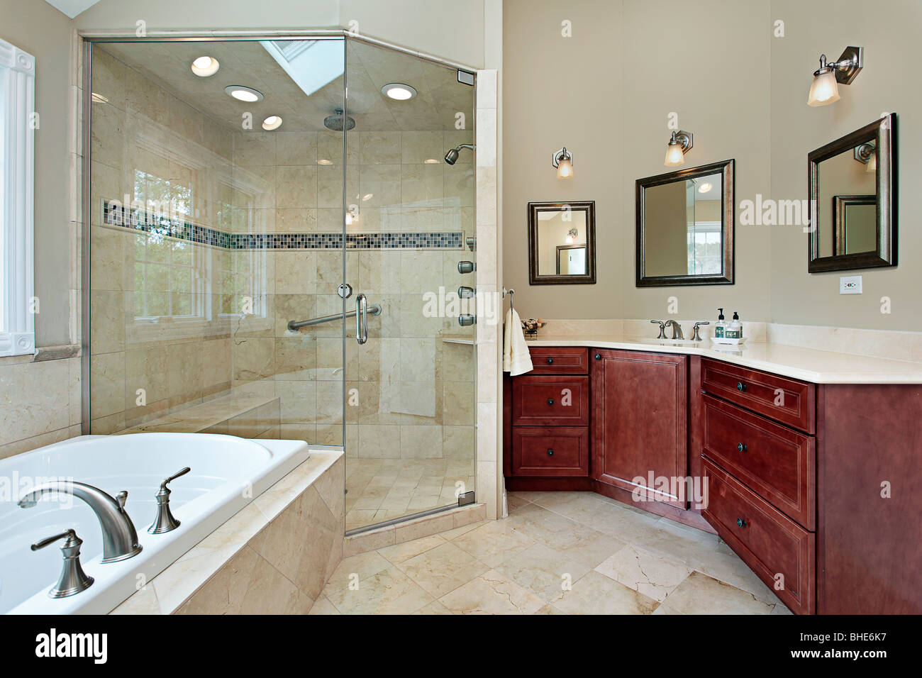 Master bath in luxury home with glass shower - Stock Image