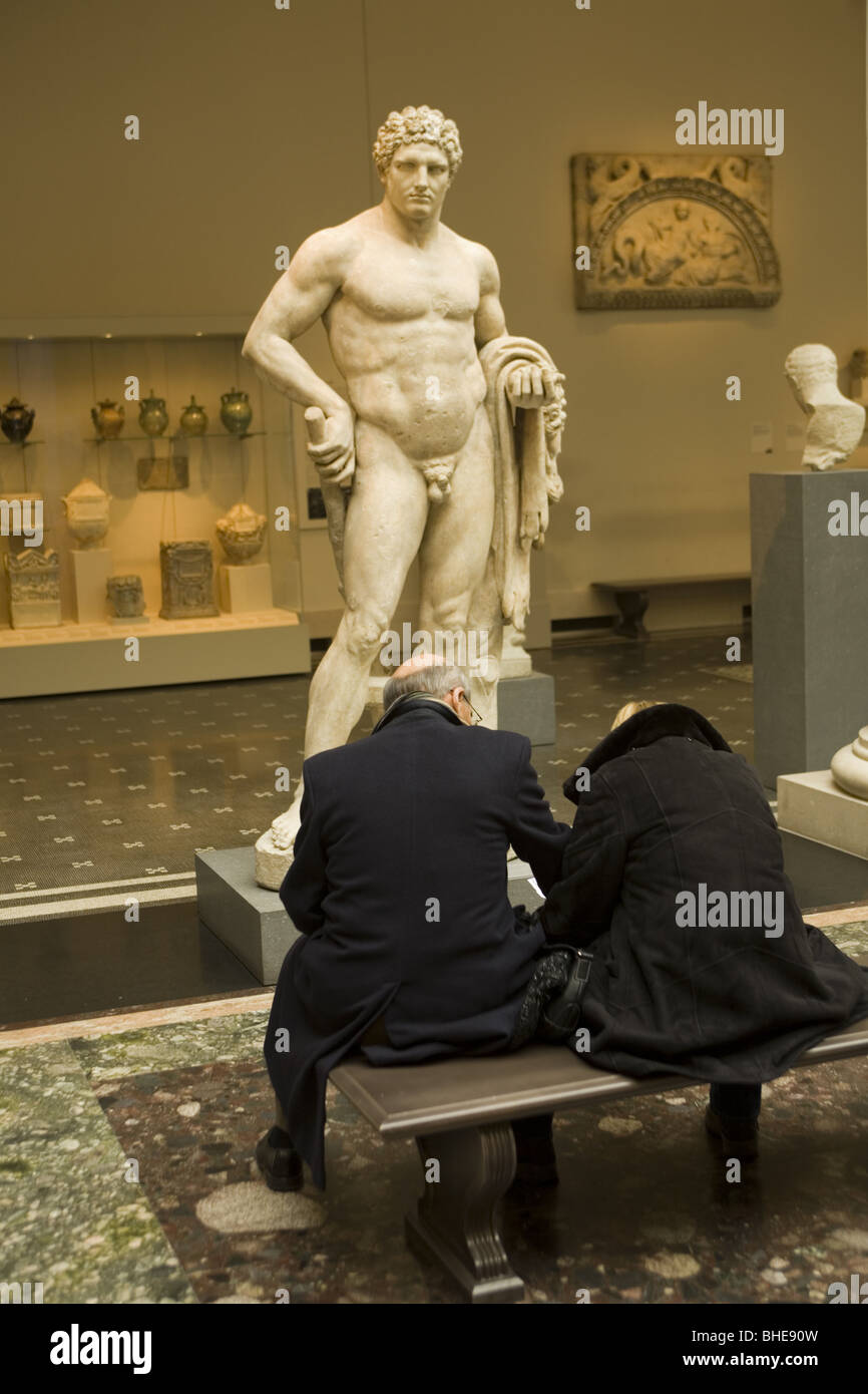 Couple sit in front of a marble statue of the young Hercules; Roman, Flavian Period, 68-98 A.D. Stock Photo
