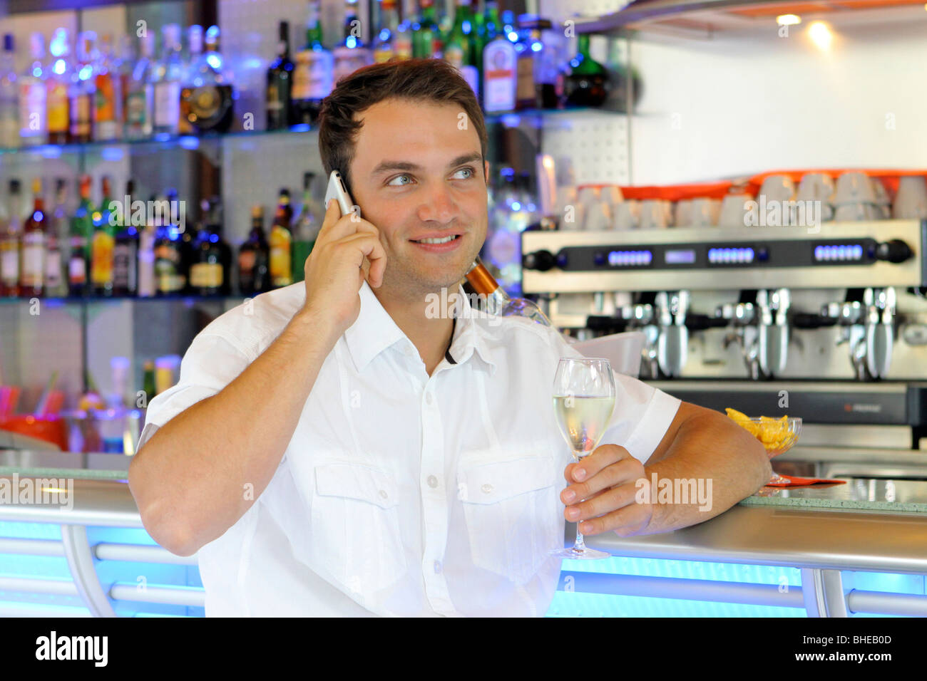 Young man with a cell phone at the bar Stock Photo