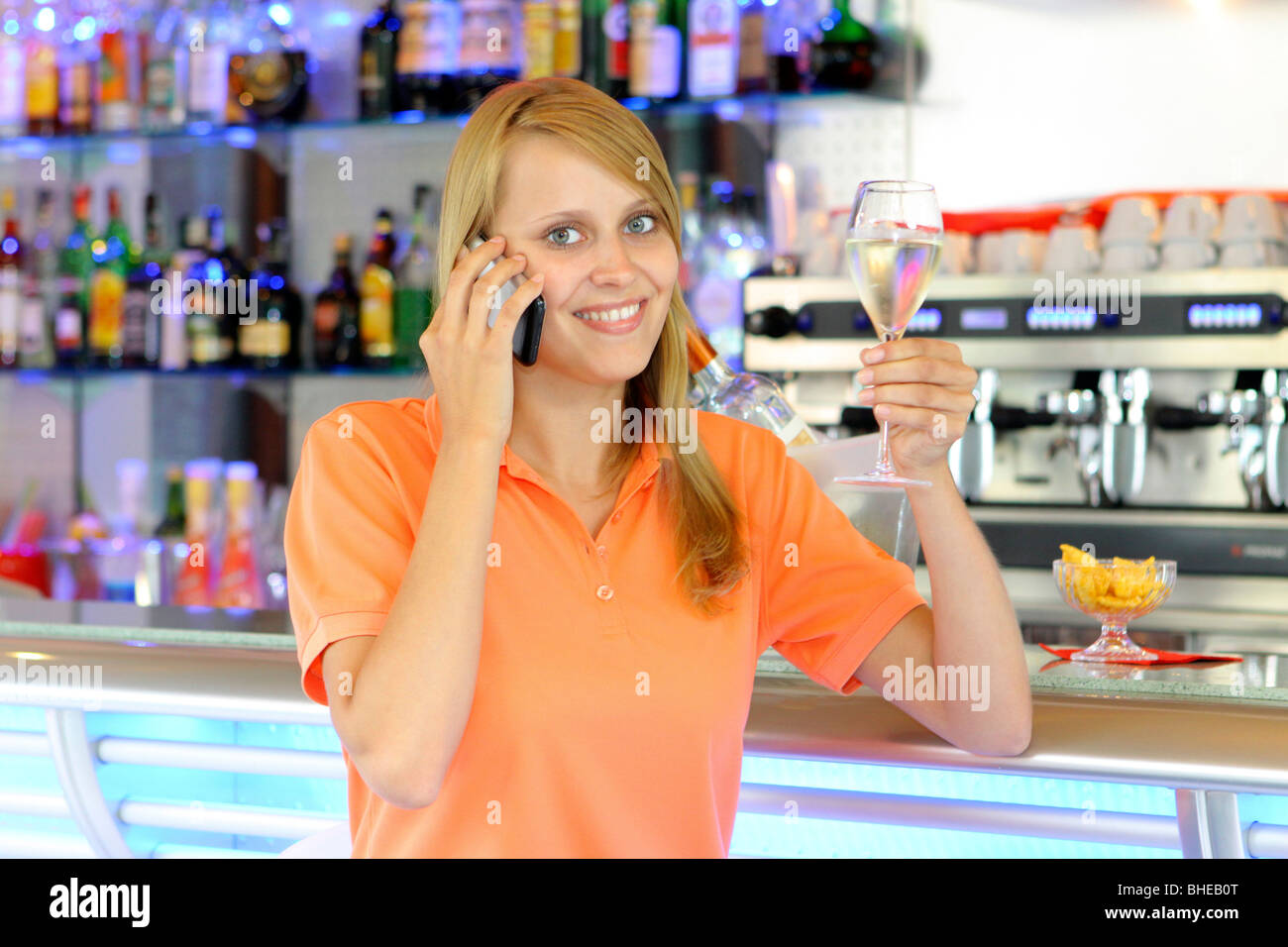Young woman with a drink and cell phone at the bar - Stock Image