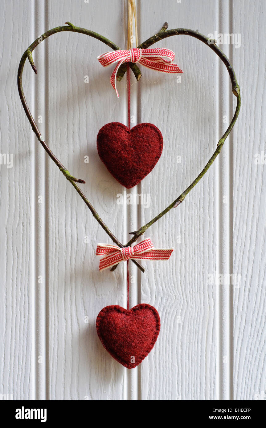 Decorative heart made of birch twigs tied with woven red and white ribbon with hanging red felt hearts - Stock Image