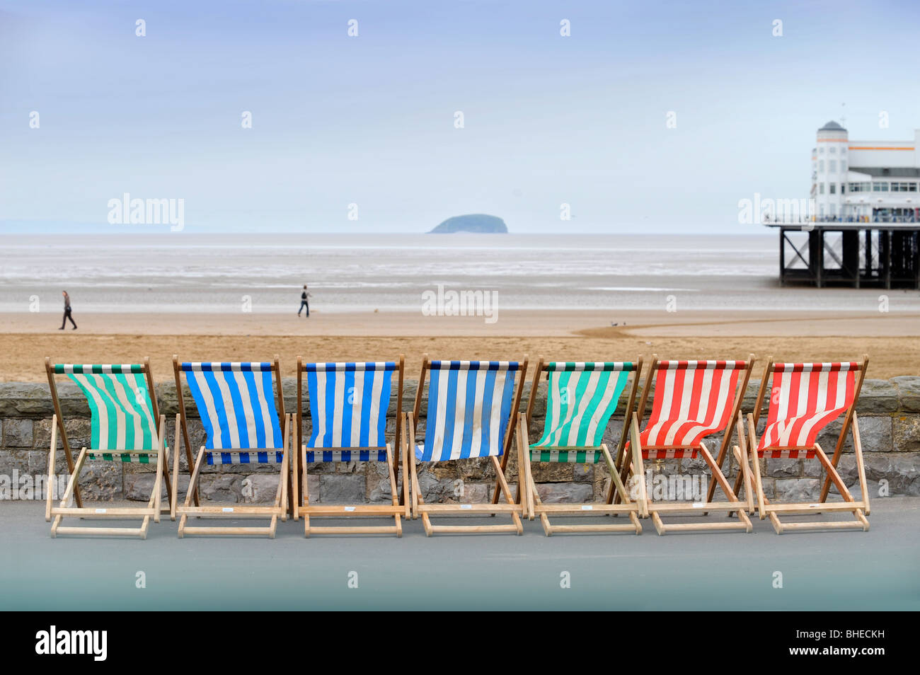 Deck chairs by the sea wall with Steep Holm island on the horizon at Weston-Super-Mare Somerset UK - Stock Image