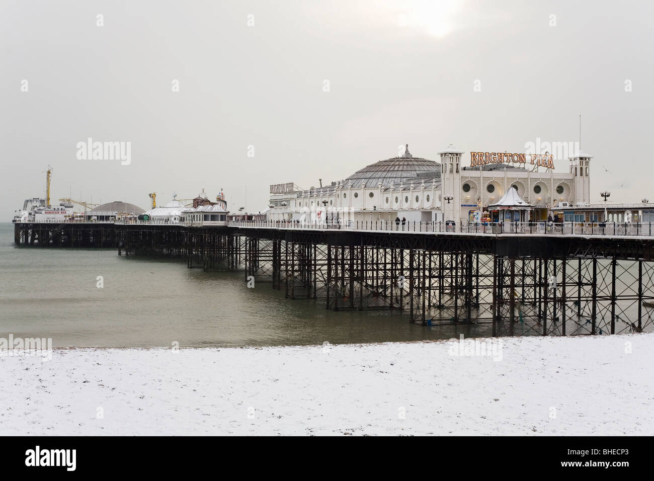 Snow lies on Brighton Beach, in front of the famous Brighton Pier, in East Sussex, England. Stock Photo