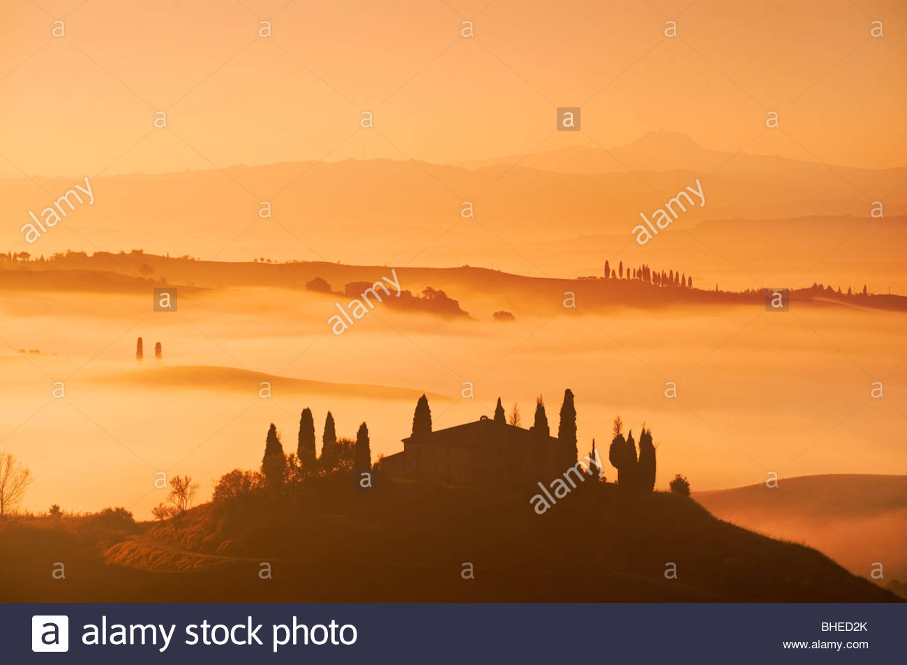 Early morning mist surrounds the farmhouse at Belvedere, near San Quirico D'Orcia, Val D'Orcia, Tuscany, - Stock Image