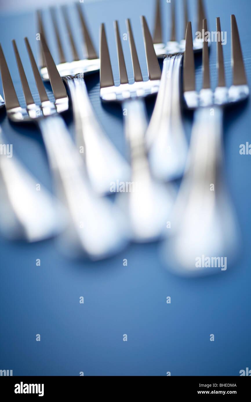 Steel forks on blue background - Stock Image