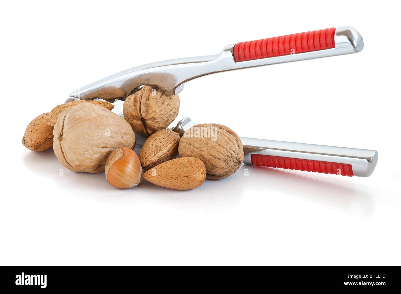 detail of nutcracker with almonds and nuts isolated on white background - Stock Image