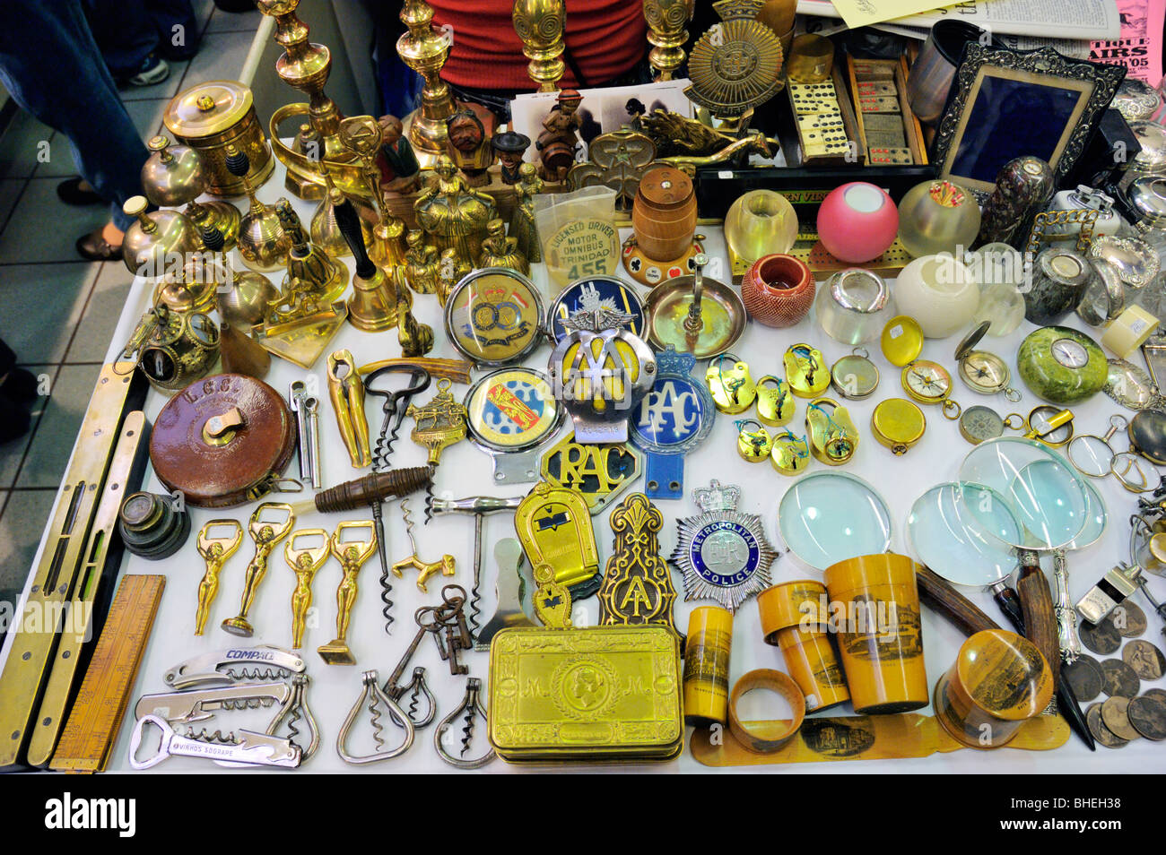 Collectables on a Portobello Road antique market stall, London, England. Items include bottle openers, corkscrews, - Stock Image
